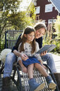 Mother and daughter sitting on chair outdoors reading book - CUF13833