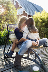 Daughter sitting on mother's lap on lounge chair on wooden decking - CUF13836