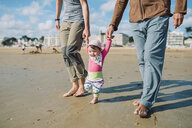 France, La Baule, baby girl walking on the beach with father and grandfather - GEMF02014