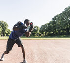 Young Afro-American man training boxing on sports field, outdoors - UUF13869