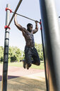 Muscular young man exercising on parcours bars - UUF13878