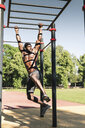 Muscular young man exercising on parcours bars - UUF13881