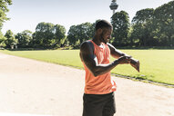 Young athlete in training on sports field taking the time on his smartwatch - UUF13893
