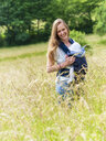 Portrait of happy mother carrying her little daughter in baby sling in nature - LAF02040