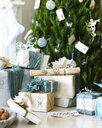 Handmade christmas gift wrapping and christmas crackers in front of christmas tree - CUF13869