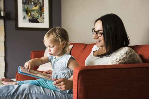 Mother teaching daughter to read book on sofa - CUF14019