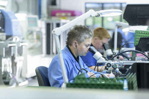 Female worker soldering component onto circuit boards in circuit board assembly factory - CUF14100