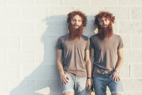 Portrait of identical adult male twins with red hair and beards against wall - CUF14208