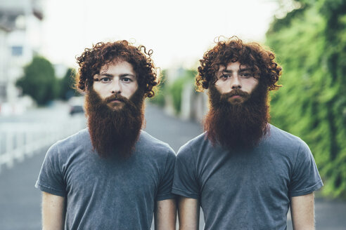 Portrait of identical adult male twins with red hair and beards on sidewalk - CUF14214