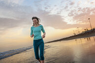 Woman running along beach at dusk, Maspalomas, Gran Canaria, Canary Islands, Spain - CUF14358
