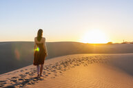 Rear view of woman strolling on dune at sunset, Maspalomas, Gran Canaria, Canary Islands, Spain - CUF14367