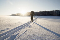 Rear view of man walking along snow tracks, Ural, Russia - CUF14379