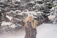 Mid adult woman arms raised throwing snow smiling - CUF14385