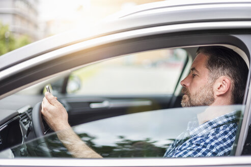 Mature man waiting in car driver seat reading smartphone text - CUF14448