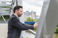 Mature businessman on footbridge texting on smartphone - CUF14454