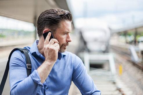 Mature businessman talking on smartphone on railway platform - CUF14466