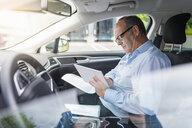 Senior male businessman updating paperwork and digital tablet in car - CUF14469