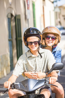 Young couple riding moped through village, Majorca, Spain - CUF14481
