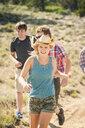 Teenage girl and adult friends running along dirt track, Bridger, Montana, USA - CUF14535