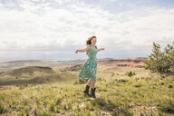 Young woman wearing dress and cowboy boots dancing in hilly landscape, Bridger, Montana, USA - CUF14544