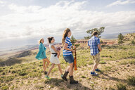 Teenage girl and young adult friends walking in hills, Bridger, Montana, USA - CUF14553