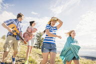 Young man and female friends playing ukulele whilst walking in hills, Bridger, Montana, USA - CUF14556