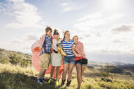Young man and female friends wrapped blanket on hill, Bridger, Montana, USA - CUF14559