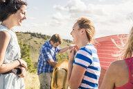 Young man and female friends preparing picnic blanket on hillside, Bridger, Montana, USA - CUF14562