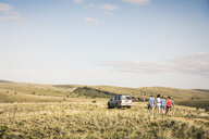 Rear view of teenage and young adult friends walking on dirt track to off road vehicle, Bridger, Montana, USA - CUF14565