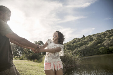 Young couple by river holding hands smiling - CUF14586