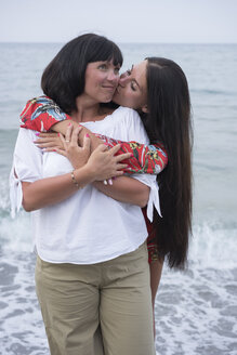 Greece, happy adult daughter kissing her mother in front of the sea - BEF00098