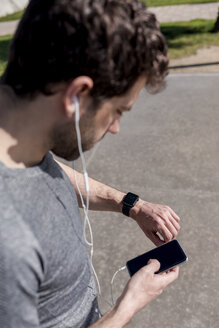 Sportive man with cell phone, earphones and smartwatch outdoors - MAUF01396
