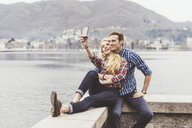 Young couple sitting on harbour wall taking smartphone selfie, Lake Como, Italy - CUF14618