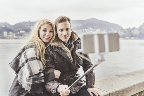 Young couple taking smartphone selfie on harbour wall, Lake Como, Italy - CUF14621