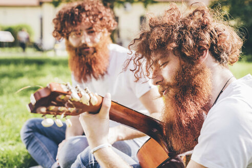Young male hipster twins with red beards sitting in park playing guitar - CUF14651