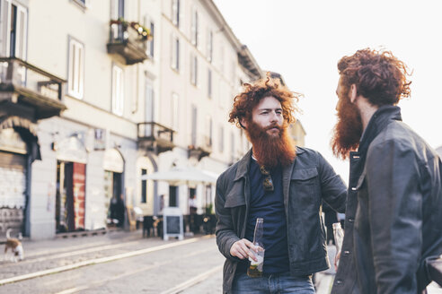 Young male hipster twins with red hair and beards talking on city street - CUF14657
