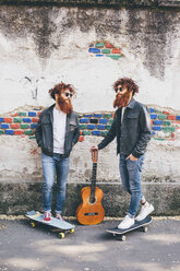Young male hipster twins with red hair and beards on sidewalk with skateboards - CUF14663