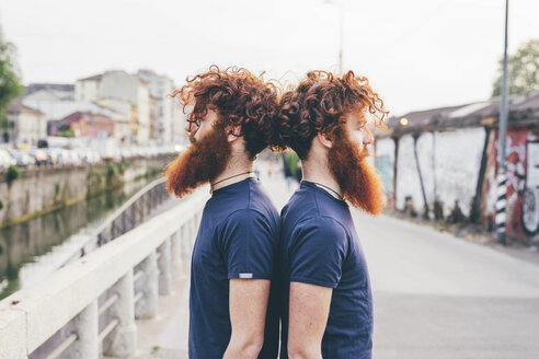 Portrait of young male hipster twins with red hair and beards back to back on bridge - CUF14666