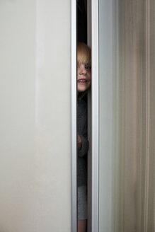 Smiling little girl hiding in wardrobe - BEF00113