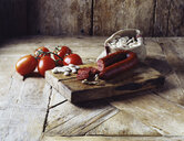 Roma tomatoes on the vine, chorizo and butter beans in burlap sack on wooden cutting board - CUF14702