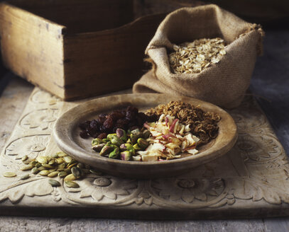 Dried fruits and nuts on wooden plate with burlap sack of oats - CUF14705