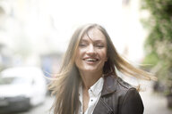 Carefree woman with long flyaway hair on city street - CUF14774