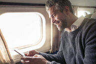 Mid adult man on airplane, using smartphone - CUF14966