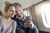 Couple on airplane, looking at smartphone, smiling - CUF14969
