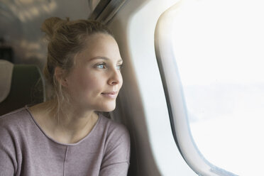 Young woman on airplane, looking out of window - CUF14972