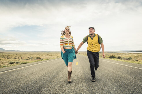 Retro style couple running hand in hand on road, Cody, Wyoming, USA - CUF15044