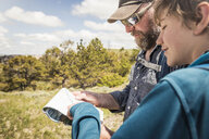 Hiking father and teenage son reading map, Cody, Wyoming, USA - CUF15047