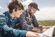 Hiking father and teenage son sitting reading map, Cody, Wyoming, USA - CUF15050