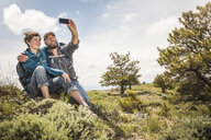 Father and teenage son taking smartphone selfie on hiking trip, Cody, Wyoming, USA - CUF15056