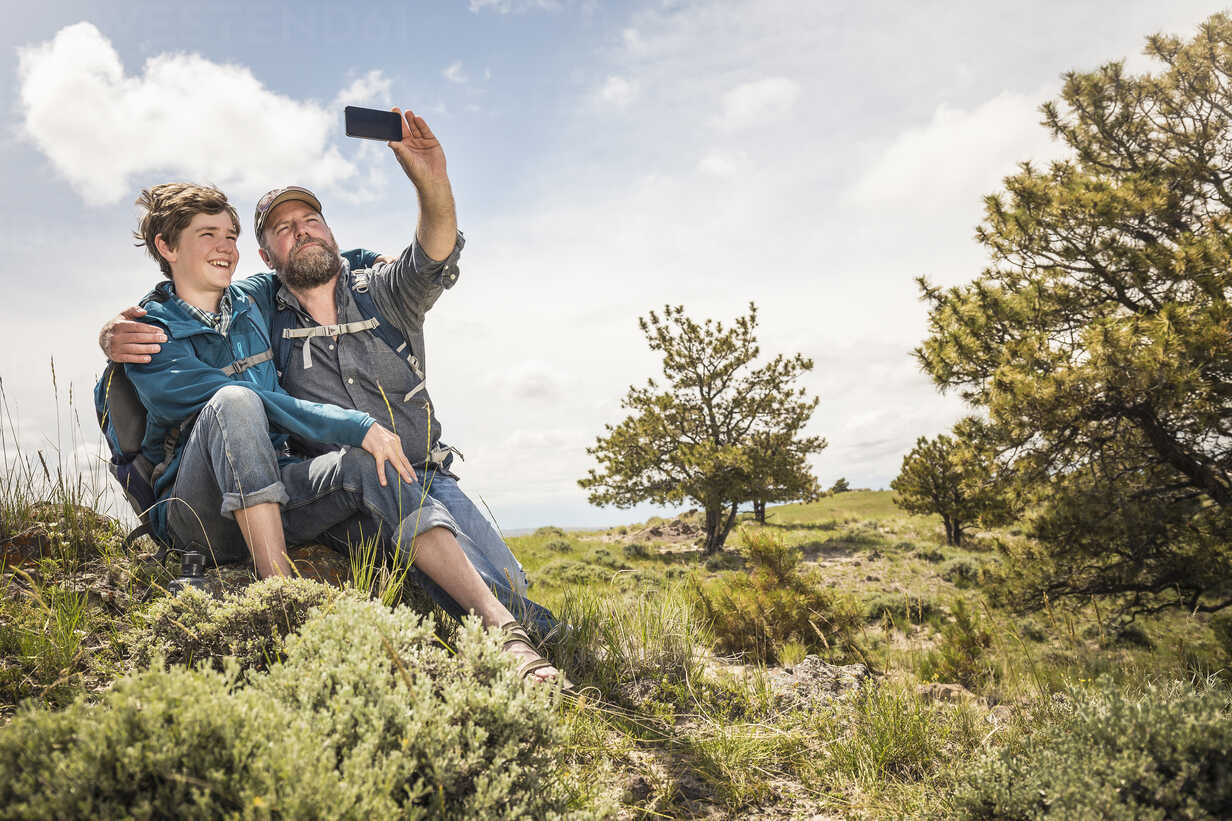 Father and teenage son taking smartphone selfie on hiking trip, Cody, Wyoming, USA - CUF15056 - SuHP/Westend61